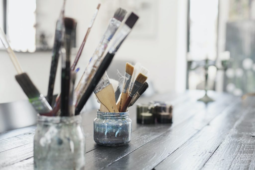 Paint brushes in containers on table