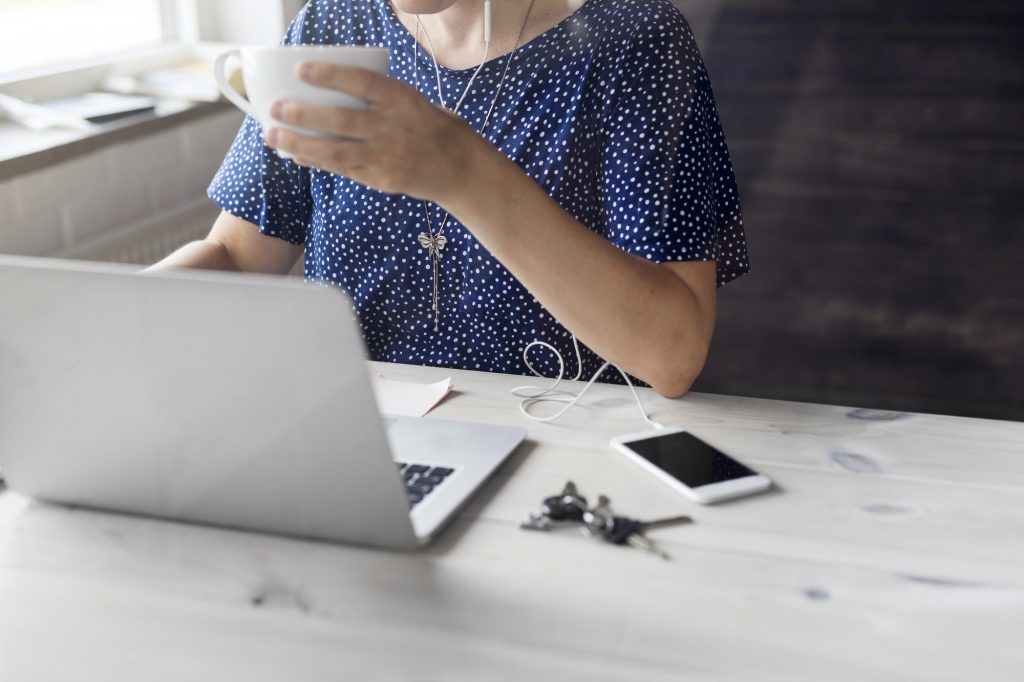 Woman drinking coffee and working on laptop