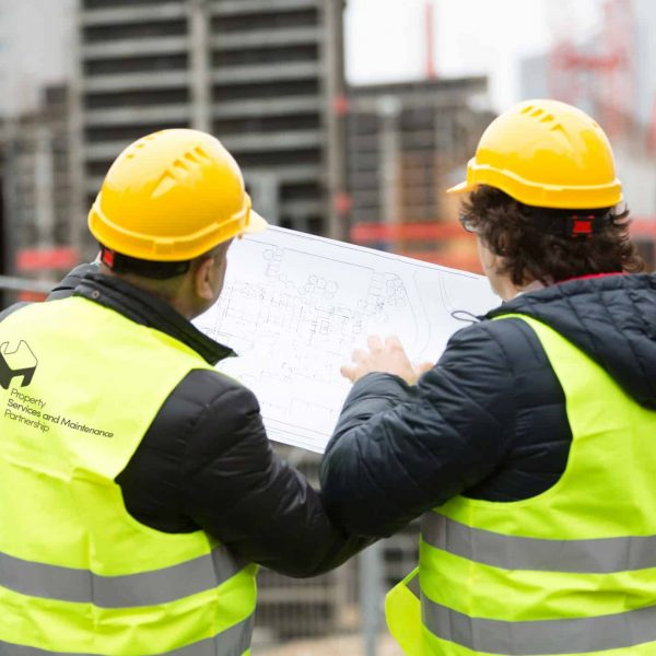 Back turned construction workers with yellow hardhat and safety jacket checking free from copyright blueprints